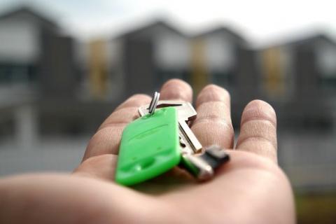 Photo d'une main tendant des clé de maison. Le compromis de vente rédigé par Immo-pop